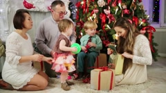 Happy family sits near Christmas tree and looks at gifts at home Stock Footage