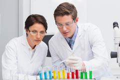 Scientists looking attentively at test tube Stock Photos