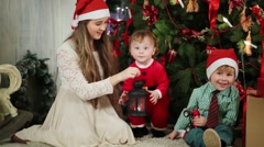 Teen girl, little boy and girl sit near Christmas tree with lamp Stock Footage