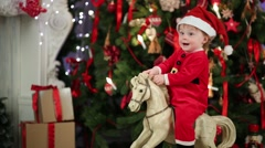 Little girl in Santa costume sits on rocking horse Stock Footage