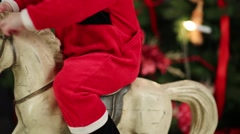 Part of body of little kid in Santa costume on rocking horse Stock Footage