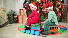 Little boy and girl in Santa costume ride on toy train Stock Footage