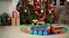 Electric toy plastic train goes on railroad near Christmas tree Stock Footage