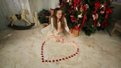 Teenage girl lights candles in shape of heart near Christmas tree Stock Footage