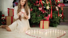 Girl lights many candles in shape of heart near Christmas tree Stock Footage