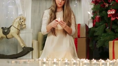 Pretty girl lights many candles on floor near Christmas tree Stock Footage
