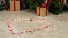 Many small candles in shape of heart on floor near Christmas tree Stock Footage