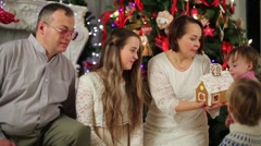 Family of five looks on gingerbread house near Christmas tree Stock Footage