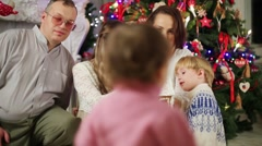 Family looks on gingerbread house in hands of mother Stock Footage