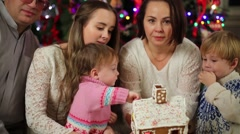 Happy family of five eats gingerbread house near Christmas tree Stock Footage