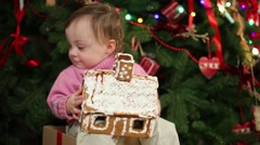 Cute little girl holds gingerbread house near Christmas tree Stock Footage
