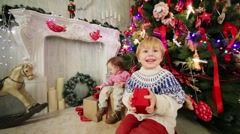 Little girl and boy with red gift boxes sit near Christmas tree Stock Footage