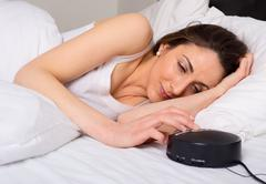 Young woman turning off the alarm clock in the morning Stock Photos