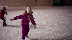 Little girl skate as bird on skating rink ice in evening - stock footage