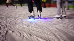 Legs of skating people and skates with illumination on skating rink Stock Footage