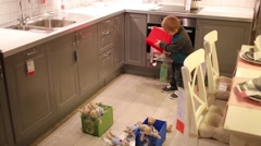 Boy plays with toys and boxes in room of shop of furniture Stock Footage