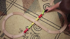 Kid hand and wooden railroad with train with magnets on carpet Stock Footage