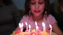 Girl makes wish and blows out candles on cake at birthday Stock Footage
