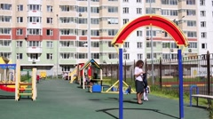 Mother and daughter at playground near residential buildings Stock Footage