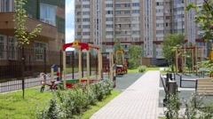 Playground near high residential buildings at summer day Stock Footage