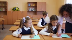 Two girls and boy write and teacher looks at exercise book Stock Footage