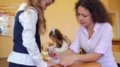 Girl sits, other girl stands and teacher writes in exercise book Stock Footage