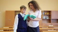 Teacher looks in exercise book and talks with boy in classroom Stock Footage