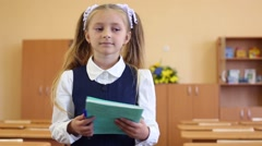 Girl in uniform stands in classroom and holds green exercise book Stock Footage
