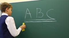 Boy stands near chalkboard in classroom at school and erases Stock Footage