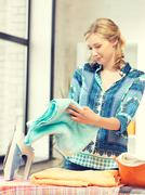 Lovely housewife with iron Stock Photos