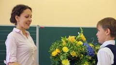 Boy presents big bunch of flowers to teacher near chalkboard Stock Footage