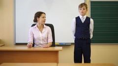 Teacher sits at table and boy stands near chalkboard and answers Stock Footage