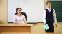 Teacher checks exercise book and boy near chalkboard at her Stock Footage