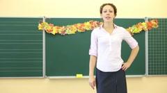 Teacher stands near chalkboard and talks in classroom Stock Footage