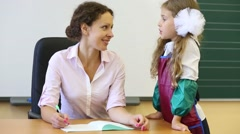 Teacher sits at table with exercise book and looks at girl Stock Footage