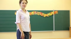 Teacher stands near chalkboard and goes in classroom Stock Footage