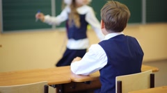 Back of boy sitting at desk and looking at girl near chalkboard Stock Footage