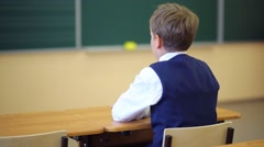 Back of boy sitting at desk and turning to camera near chalkboard Stock Footage