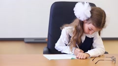 Girl in vest sits at teacher table and writes in exercise book Stock Footage