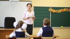 Teacher talks near chalkboard and two pupils listen her Stock Footage
