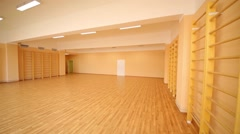 Empty school gymnasium with yellow floor and climbing near walls Stock Footage
