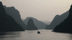 Boat in peaceful Halong bay at sunset Stock Footage