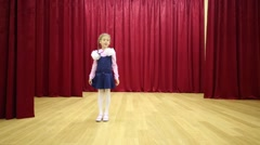 Happy girl with braids and bows performs on stage with curtains Stock Footage