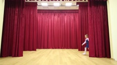 Happy girl in uniform enter stage with red curtains and perform Stock Footage
