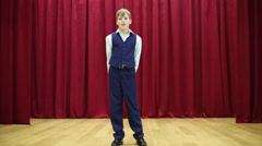 Stock Video Footage of Serious boy in suit with vest performs on stage with red curtains