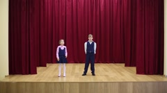 Girl and boy in school uniform perform on stage Stock Footage