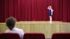 Back of woman looking on performing boy and girl on stage. Stock Footage