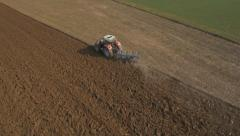 Aerial - Preparing field for planting crops with agricultural machinery Stock Footage