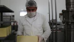 Production yellow cheese. Worker packaging cheese on conveyor line in dairy. - stock footage