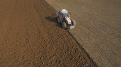 Aerial - Loosening and aerating top layers of soil with a tractor - stock footage